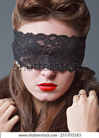 Close up portrait of a charming woman in black lace mask.