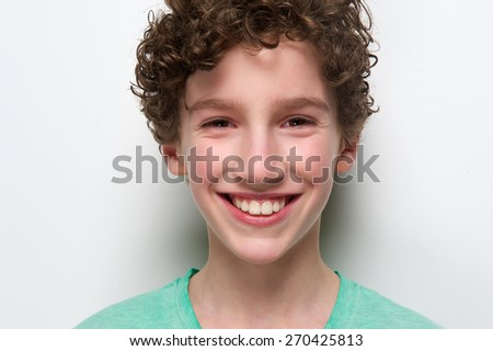 Close up portrait of a cheerful boy smiling against white background  - stock photo