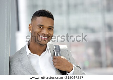 Close up portrait of a cheerful young man smiling with bag - stock photo