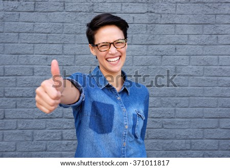 Close up portrait of a cheerful young woman with thumbs up hand gesture - stock photo