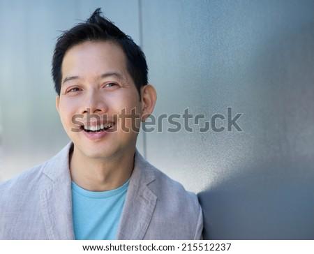 Close up portrait of a confident asian man smiling - stock photo
