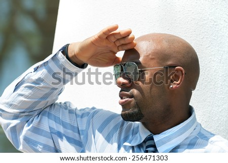 Close up portrait of a confident business man wearing sunglasses in the city. - stock photo