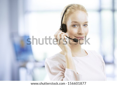 Close-up portrait of a confident young female customer service agent with headset working in office - stock photo