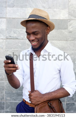 Close up portrait of a cool young african guy with hat and bag looking at mobile phone against gray background - stock photo