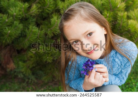 Close up portrait of a cute little girl, holding small bouquet of violets, wearing blue pullover - stock photo
