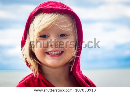 Close-up portrait of a cute, smiling young child at the beach in a red top. - stock photo