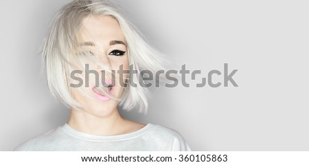 Close-up portrait of a fashion blonde with stylish short hairstyle on gray background  - stock photo