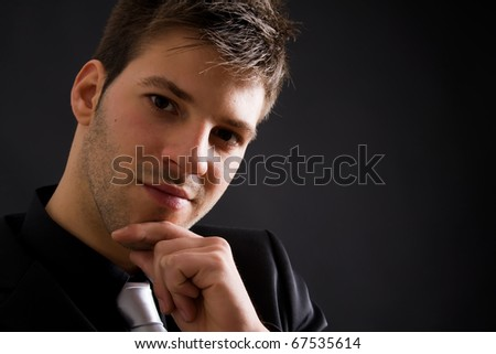 Close up portrait of a fashion young businessman black suit casual tie on black background - stock photo