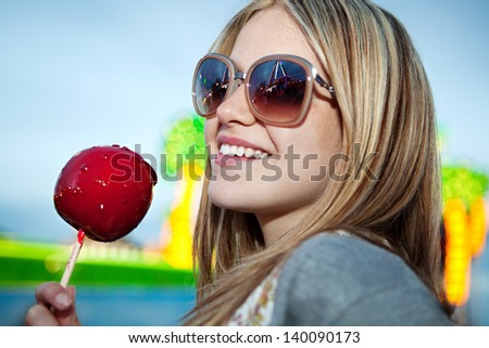 Close up portrait of a fashionable young woman in an amusement park arcade ground wearing sunglasses with reflections of rides and lights, holding a red caramel apple during evening night time. - stock photo