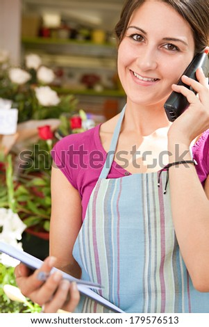 Close up portrait of a florist business woman working at her flower market store, using a phone to have a conversation and order stock. Business owner running a retail shop, outdoors. - stock photo