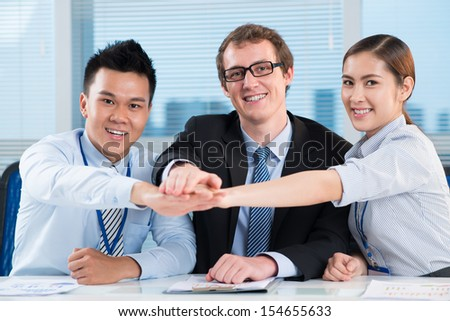 Close-up portrait of a friendly business team smiling and looking at camera on the foreground - stock photo