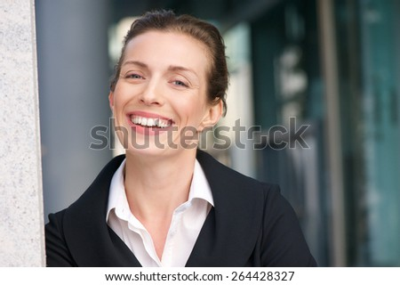 Close up portrait of a friendly business woman smiling with black jacket and white shirt - stock photo