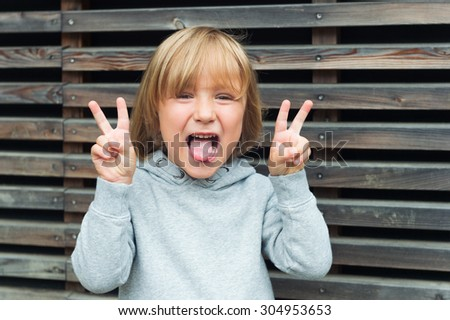 Close up portrait of a funny little boy, wearing grey sweatshirt, pulling a tongue and gesturing peace sign - stock photo