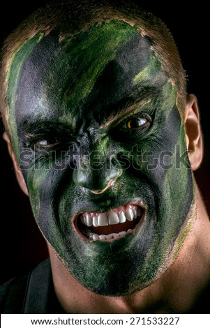 Close-up portrait of a furious soldier in war paint. Black background. Military, war. Special forces. - stock photo