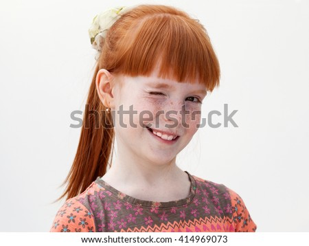 Close up portrait of a ginger girl winking - stock photo