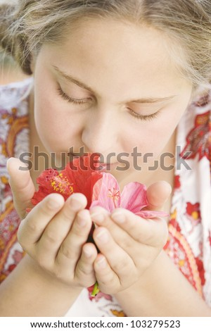 Close up portrait of a girl smelling red and pink hibiscus flowers in her hands. - stock photo
