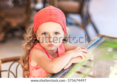 Close up portrait of a grimacing girl in neon pink dress - stock photo