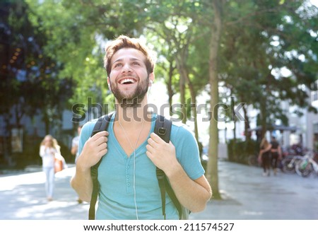 Close up portrait of a handsome young man walking outdoors with backpack - stock photo