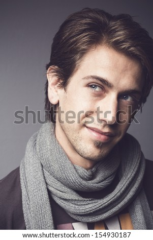 Close up portrait of a handsome young man with a thoughtful sympathetic expression wearing a warm winter scarf looking upwards - stock photo