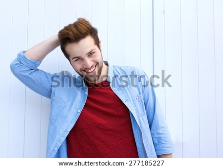 Close up portrait of a handsome young modern man smiling with hand in hair - stock photo