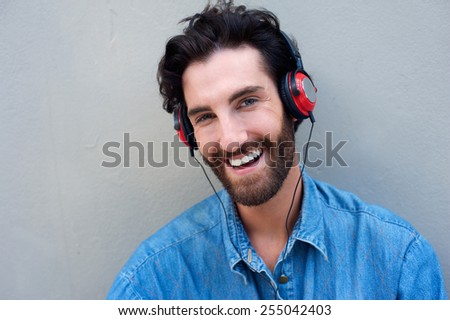 Close up portrait of a happy man smiling while listening to music with headphones - stock photo