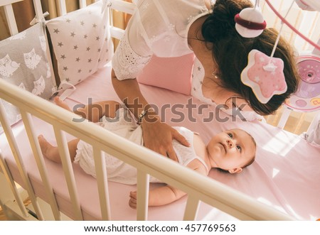 Close-up portrait of a happy mother laughing with cute baby in crib - stock photo