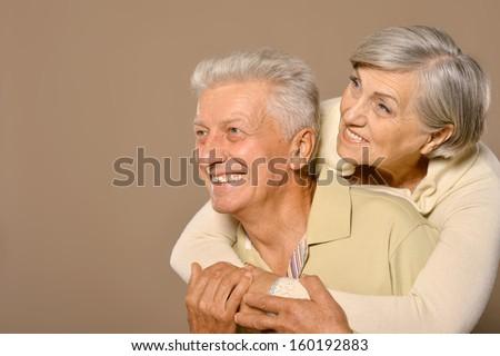 Close-up portrait of a happy senior couple on grey background - stock photo