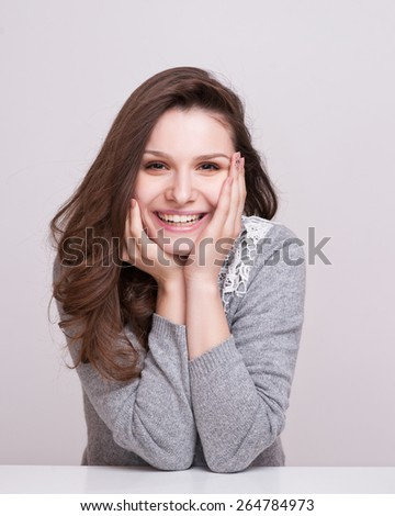 Close up portrait of a happy smiling woman resting her chin on her hands and looking directly at the camera - stock photo
