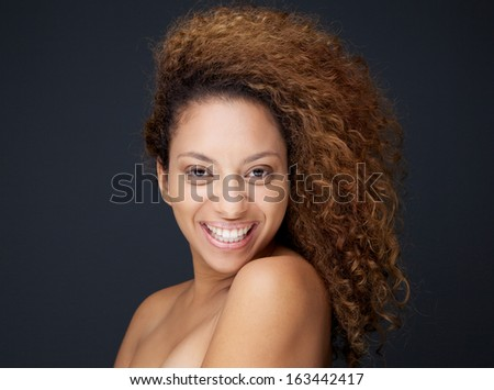 Close up portrait of a happy woman with curly hair smiling on gray background - stock photo