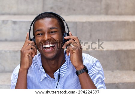 Close up portrait of a happy young african american man laughing with headphones - stock photo