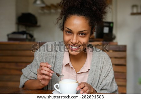 Close up portrait of a happy young african american woman with cup of coffee - stock photo