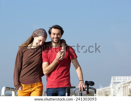 Close up portrait of a happy young couple walking outdoors - stock photo