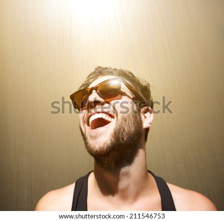 Close up portrait of a happy young man smiling with sunglasses - stock photo