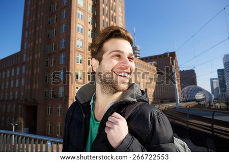 Close up portrait of a happy young man walking in the city with bag - stock photo