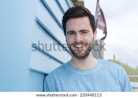 Close up portrait of a happy young man with beard smiling outdoors - stock photo