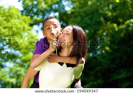 Close up portrait of a happy young mother with son piggybacking and blowing dandelion - stock photo