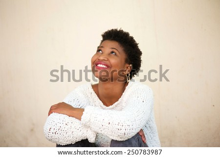 Close up portrait of a happy young woman smiling and looking up - stock photo