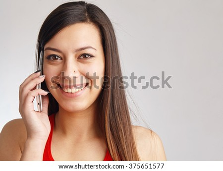 Close up portrait of a happy young woman talking on the phone. - stock photo