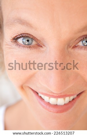 Close up portrait of a joyful healthy woman with fresh skin smiling at the camera feeling confident. Wellness and well being care and aging wrinkles with a cheerful expression, indoors. - stock photo