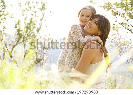 Close up portrait of a joyful mother and daughter relaxing together in a beautiful spring field of grass and flowers, hugging and enjoying a sunny holiday outdoors. Family love and lifestyle. - stock photo