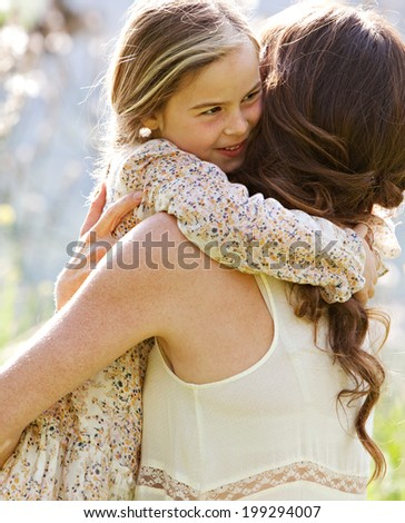 Close up portrait of a joyful mother and daughter relaxing together in a beautiful spring field of grass and flowers, hugging on a sunny holiday outdoors. Family love and holiday activities lifestyle. - stock photo