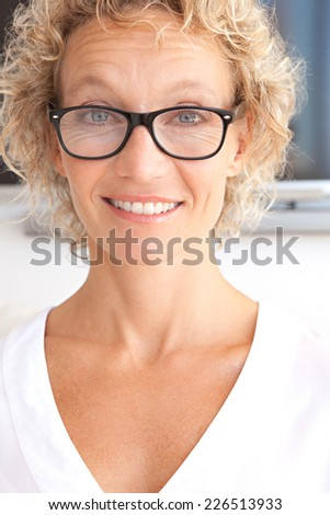 Close up portrait of a joyful professional successful woman smiling at the camera feeling confident in an office interior. Business woman with reading glasses and a cheerful face expression, indoors. - stock photo