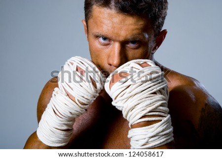 Close-up portrait of a kick-boxer in a fighting stance. Kickboxing or muay thai - stock photo