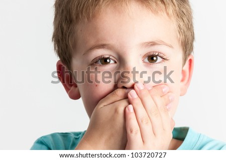 Close-up portrait of a little boy with hands on mouth - isolated on white background - stock photo