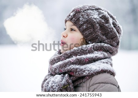 Close-up portrait of a little girl in brown jacket and knit scarf and hat on a background of a snow park - stock photo