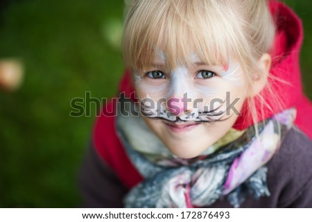close up portrait of a little girl with watercolor on her face  - stock photo