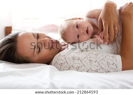 Close up portrait of a loving mother resting with baby in bed - stock photo