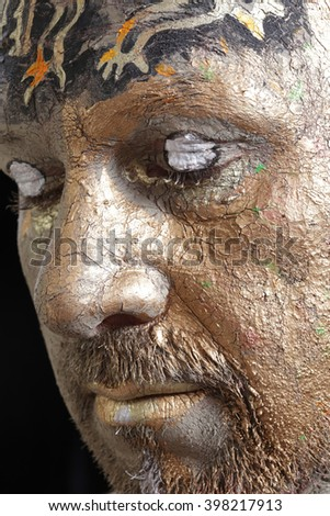 close-up portrait of a man in the clay body art , studio on a dark background - stock photo