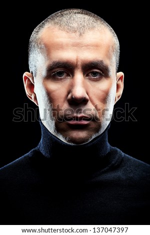 Close-up portrait of a man over black background. - stock photo