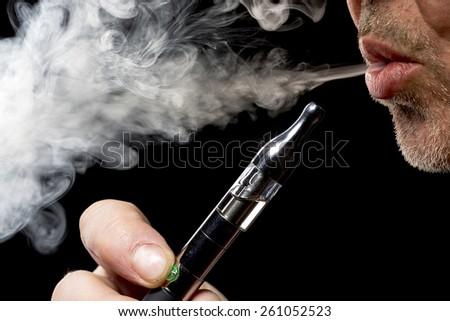 close up portrait of a man smoking an e-cigarette - stock photo
